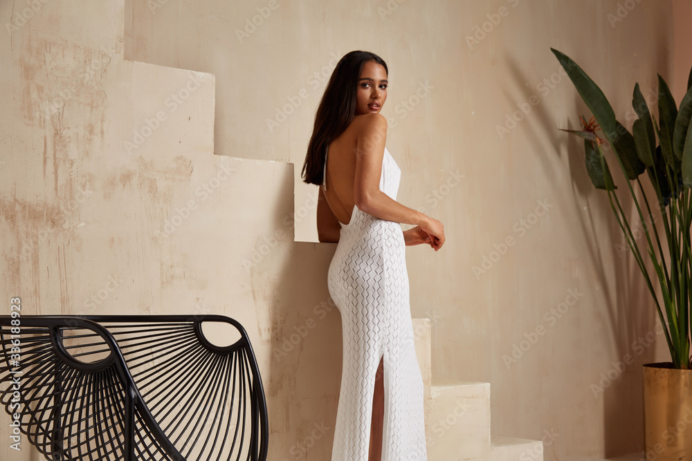 Fototapeta Sexy beautiful woman brunette tanned skin makeup cosmetic fashion clothes summer collection white cotton dress accessory bag style summer journey walk date beach wear interior stairs leaves flowerpot.