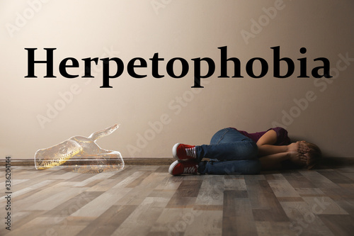 Scared little girl suffering from herpetophobia on floor indoors Canvas Print