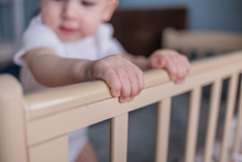 The Baby Stands In A Crib And ...