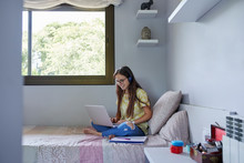 Female Teenager Studying In Her Bed