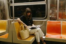 Woman With Bangs Sitting Reading On A Subway Car With A Basket