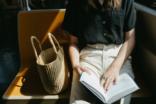 Woman Sitting On The Train In The Sun With A Basket Reading A Book