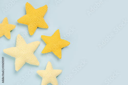 Knitted toy yellow stars on blue . background. Baby stuff and accessories. Flat lay, top view