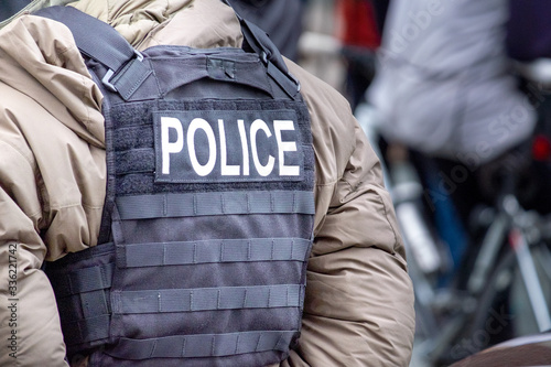 Fotografie, Obraz A police officer wearing a khaki parka down-filled uniform and a black bulletproof vest with the word police on the back