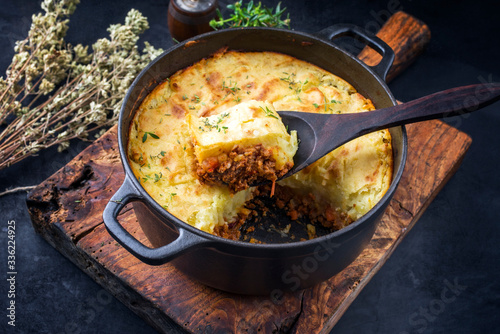 Stampa su Tela Traditional English shepherd pie offered as closeup in a Dutch oven on a wooden