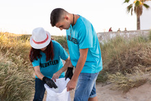 Two Volunteers Collecting Plastic Waste During Beach Clean Up