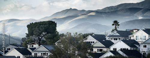 Photo Contrasting angular houses against soft hills.