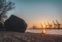 Germany, Hamburg,?Alter Schwede Boulder On Riverside Beach At Sunrise With Silhouettes Of Harbor Cranes In Background