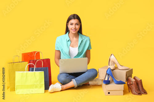 Fototapeta Young woman with laptop, shopping bags and new shoes on color background obraz