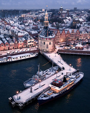 "Aerial View Of Snowy Houses And ""De Hoofdtoren"" In Hoorn Harbour, Noord-Holland, Netherlands, With Boats On The Dock"