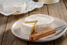 Camembert Cheese On White Plate With A Knife On A Wooden Table