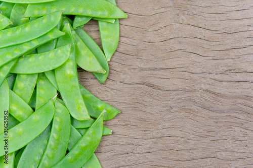 Leinwand Poster Sugar Pea, Snow peas on plank wooden background