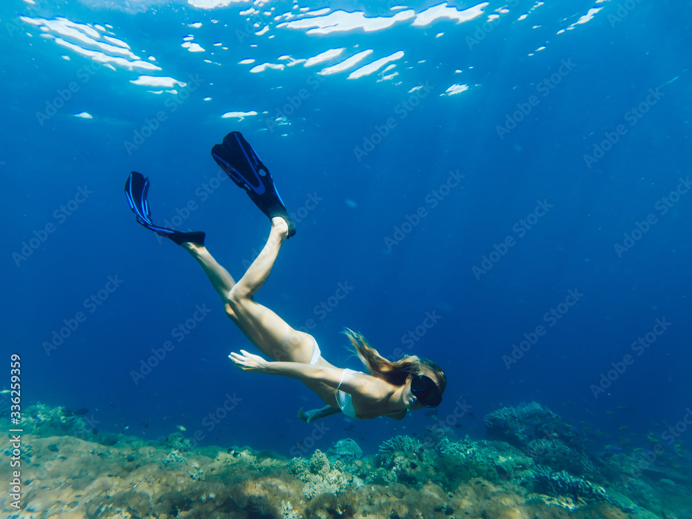 Fototapeta Female tourist love extreme sport practicing scuba diving during holiday on Bahamas, woman in swim flippers exploring ocean depth enjoying Indonesian adventure for discovering aquatic nature life