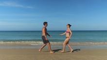 Joyful Young Couple Runs Towar...
