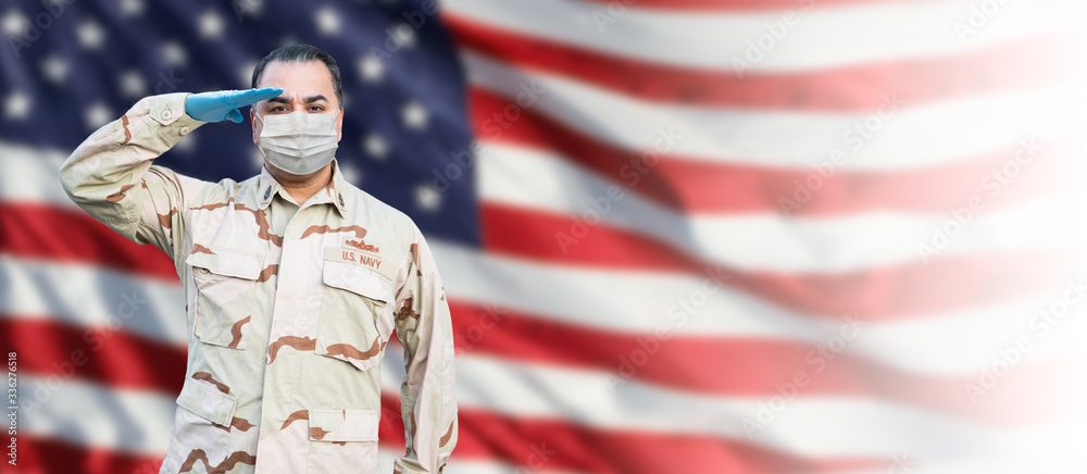 Fototapeta Male Navy Medical Personel Saluting Wearing Personnel Protective Exquipment (PPE) With American Flag Background Banner