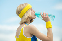 Fitness Woman. Midsection Of Sporty Woman With Measure Tape Around Waist Holding Water Bottle In Park Over Sky Backgroung.