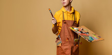Young Teen Boy Painter In Yellow Hoodie And Jumpsuit Standing And Holding Easel, Paint And Brush In Hands Over Yellow Background