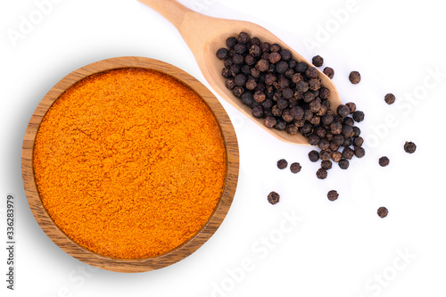 Leinwand Poster curcumin powder ( tumeric ground, turmeric, Curcuma ) in wooden bowl and black pepper corn in  spoon isolated on white background