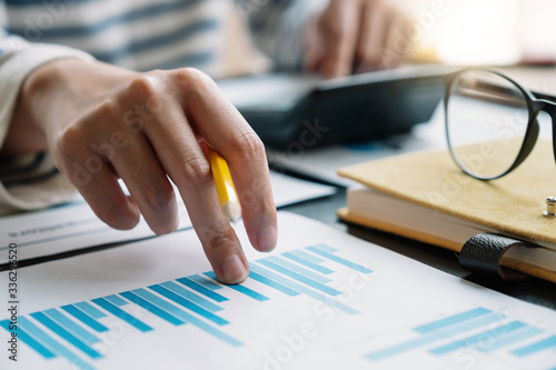 Obraz Business woman working in finance and accounting Analyze financial budget with calculator in the office - fototapety do salonu