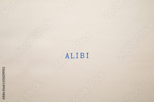 Photo a ALIBI word stamped on a piece of paper.