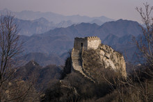 A Ruined Section Of The Great Wall Of China With An Ancient Tower Built On Top Of A Mountain Range With Blue Mountains In The Background.