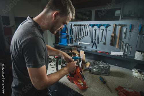 Fototapeta Professional serviceman is repairing a chainsaw using a spanner to untighten screw. Man fixing a chainsaw in a fancy workshop obraz