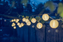 Row Of Round Paper Lanterns In A Home Garden On A Wooden Thatched Background At Night. Festive Decoration In The Garden On An Evening.