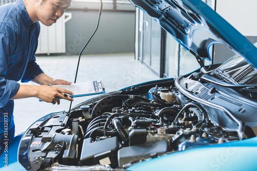 Fotografie, Obraz Asian Man mechanic inspection writing note on clipboard