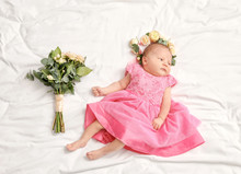 Cute Little Baby Girl With Beautiful Flowers Lying On Bed