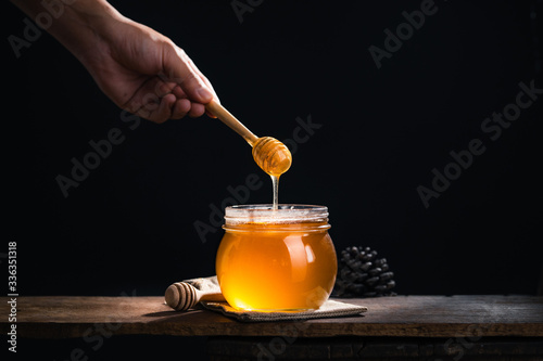 Fotografia Honey in a glass jar,Scoop the honey in a glass jar