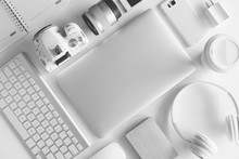 Flat Lay Of White Office Desk Table With Many White Gadgets