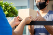 Asian Delivery man wearing mask send a package holding parcel cardboard on front receiver shipping deliver cargo social distancing while the virus is spreading medical concept.