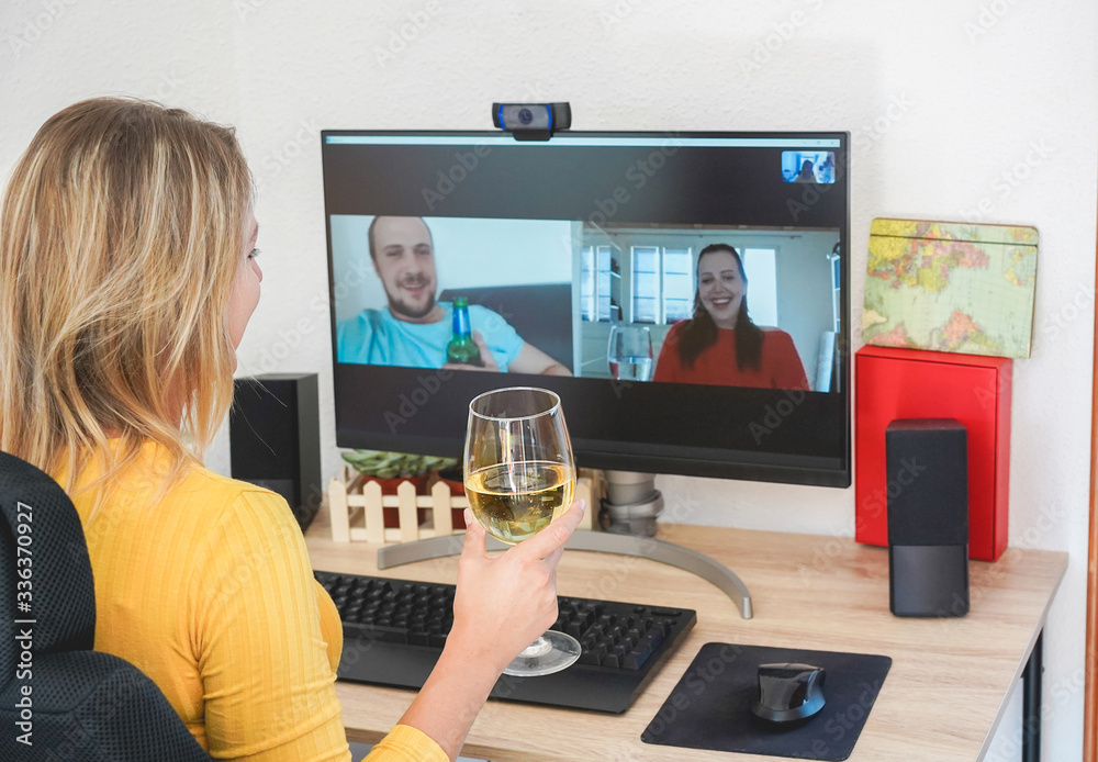 Fototapeta Young woman chatting maging video call with friends while drinking wine and laughing together - Alternative party during home isolation quarantine - Focus on glass hand