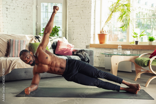 Fényképezés African-american man teaching at home online courses of fitness, aerobic, sporty lifestyle while being quarantine