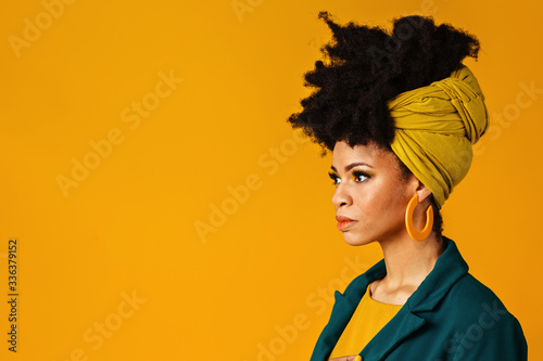 Profile portrait of a serious young woman with big yellow earrings and afro hair Canvas Print