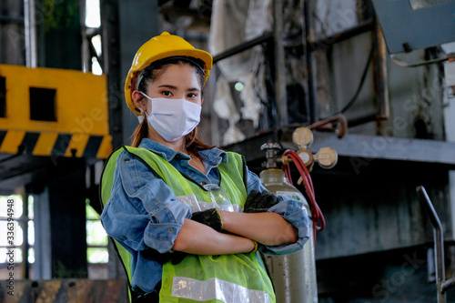 Papel de parede Factory woman worker or technician with hygienic mask stand with confident action sometime as engineer in workplace during concern about public health of corona virus pandemic in people