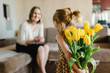 Cute little girl greeting mother and gives her a bouquet of flowers tulips at home. Mother's day concept. Mom and daughter smiling. Happy family holiday and togetherness. Back view.