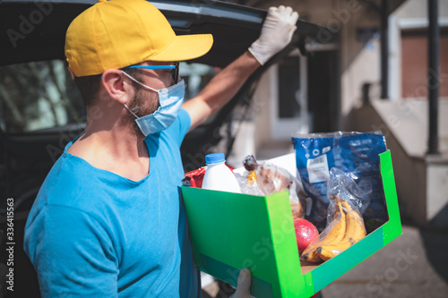 Fotomural Delivery guy with protective mask and gloves delovering groceries during lockdown and pandemic