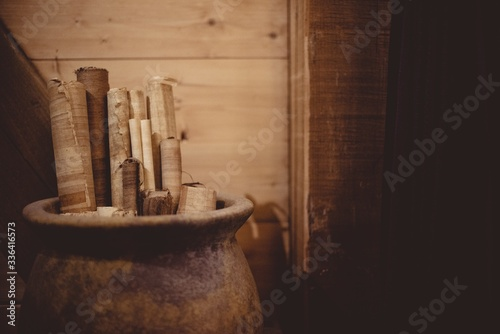 Closeup of parchment rolls in a clay pitcher under the lights with a blurry back Canvas Print