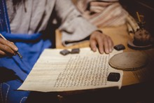 Closeup Of A Person Writing In Hebrew On An Aged Paper On The Table Under The Lights