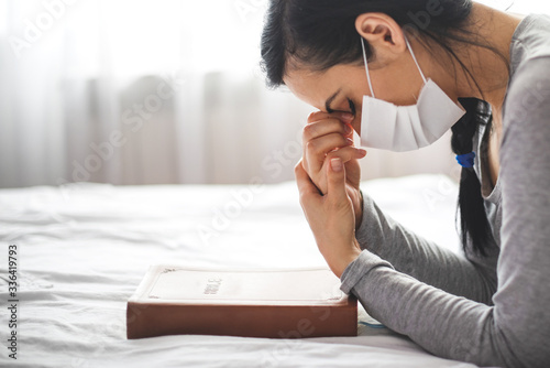 Woman with mask praying next to bed with her bible near. Fototapete