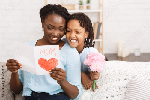 Black girl congratulating her mom with flowers and card