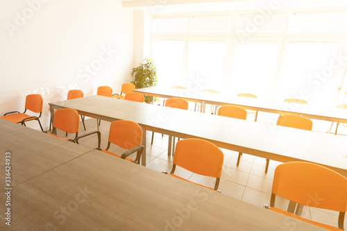 Empty desks and chairs in high key cafeteria room Fotobehang