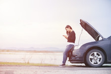 Asian Woman Is Using A Telephone To Call The Car Mechanic. For Fixing Damaged Cars On The Road