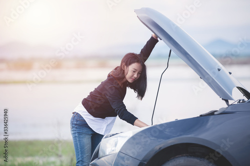 Fototapeta Asian woman checking broken down car on street