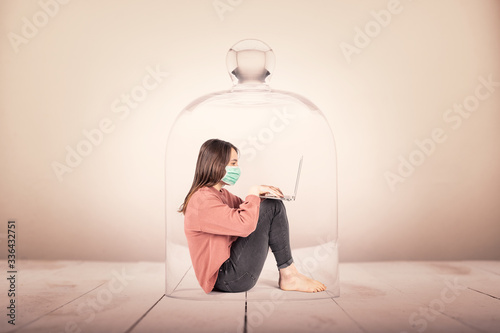 young girl with face mask using a laptop in a glass container. Coronavirus continuation concept. © xavier gallego morel