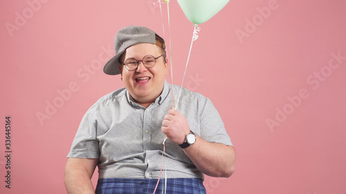 Photo Cheerful plump man very similar to Winnie the Pooh with balloons, isolated on a pink background, grimaces in the Studio