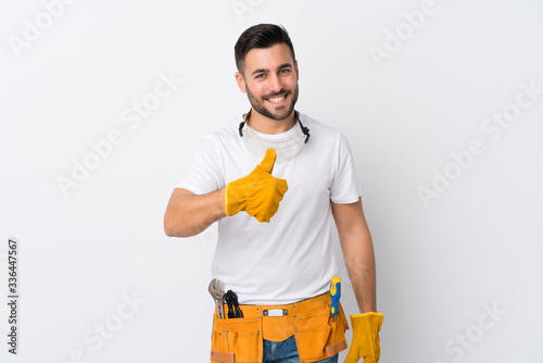 Obraz Craftsmen or electrician man over isolated white background giving a thumbs up gesture - fototapety do salonu