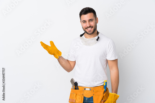 Obraz Craftsmen or electrician man over isolated white background holding copyspace imaginary on the palm - fototapety do salonu
