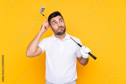 Leinwand Poster Golfer player man over isolated yellow background having doubts and with confuse